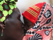 En kvinde bruger ventetiden til majsuddelingen med at kærtegne sin baby
